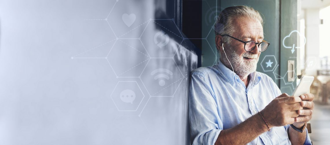 Elderly man watching an online movie from his phone